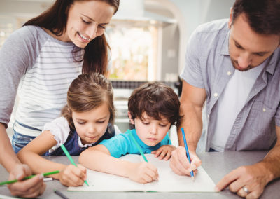 Family writing in book while standing at table in house